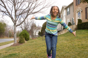 Young African-American girl in front of row homes