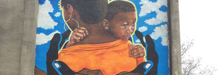 mural of woman holding child in the hand of others